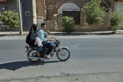 La famiglia iraniana guida un motociclo lungo la via di Yazd, Iran Immagini Stock