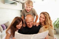 La famiglia legge il giornale a casa fotografia stock