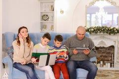 La famiglia moderna e mobile, i due figli ed il marito e la moglie sono occupati Fotografia Stock Libera da Diritti