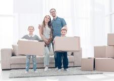 La famiglia muove le scatole verso un nuovo appartamento fotografia stock libera da diritti