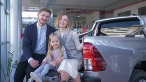 La famiglia nella sala d'esposizione dell'automobile, ritratto dei genitori sorridenti con la ragazza del bambino sceglie l'autom
