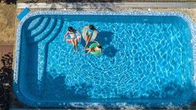 La famiglia nella vista aerea del fuco della piscina da sopra, in madre ed in bambini felici nuota sulle guarnizioni di gomma piu immagini stock