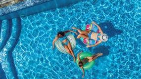 La famiglia nella vista aerea del fuco della piscina da sopra, in madre ed in bambini felici nuota sulle guarnizioni di gomma piu fotografia stock libera da diritti