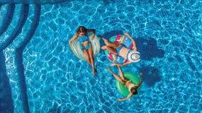 La famiglia nella vista aerea del fuco della piscina da sopra, in madre ed in bambini felici nuota sulle guarnizioni di gomma piu immagini stock libere da diritti