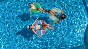 La famiglia nella vista aerea del fuco della piscina da sopra, in madre ed in bambini felici nuota sulle guarnizioni di gomma piu fotografie stock libere da diritti