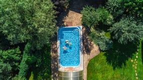 La famiglia nella vista aerea del fuco della piscina da sopra, in madre ed in bambini felici nuota sulle guarnizioni di gomma piu fotografia stock