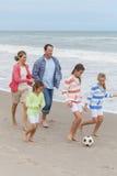 La famiglia Parents i bambini che giocano il calcio di calcio della spiaggia Immagine Stock