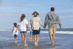 La famiglia Parents i bambini della ragazza che camminano sulla spiaggia Immagini Stock