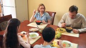 La famiglia pranza a casa nella sala da pranzo Adolescenti dei bambini, gemelli ed i loro genitori video d archivio