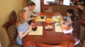La famiglia pranza a casa nella sala da pranzo Adolescenti dei bambini, gemelli ed i loro genitori archivi video