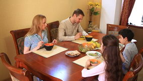 La famiglia pranza a casa nella sala da pranzo Adolescenti dei bambini, gemelli ed i loro genitori stock footage