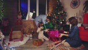 La famiglia prepara i regali e decora l'albero di Natale stock footage