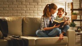 La famiglia prima della madre andante a letto legge al libro n della figlia del bambino fotografia stock