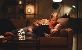 La famiglia prima della madre andante a letto legge al suo libro del figlio del bambino vicino ad una lampada nella sera fotografia stock libera da diritti