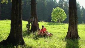 La famiglia riposa con le biciclette nella foresta dell'estate un giorno soleggiato archivi video