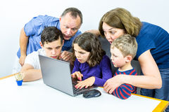 La famiglia riunita intorno al computer portatile esamina il contenuto scioccante su Internet, colpo dello studio fotografia stock libera da diritti
