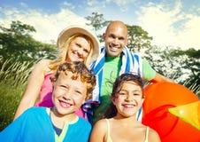 La famiglia scherza il concetto allegro dell'estate del parco dei genitori Fotografia Stock