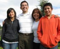 La famiglia si leva in piedi su erba contro la casa Immagini Stock