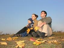 La famiglia si siede con i fogli di autunno Fotografie Stock Libere da Diritti
