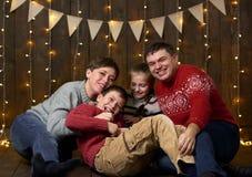 La famiglia si siede insieme su fondo di legno con le luci di festa e bandiere e divertiresi Fotografie Stock