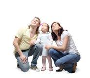 La famiglia si siede, mani della stretta ed osservare in su Fotografia Stock Libera da Diritti
