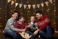 La famiglia si siede su fondo di legno scuro con le luci di festa e bandiere e divertiresi Fotografia Stock