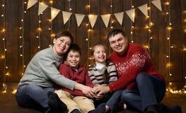 La famiglia si siede su fondo di legno scuro con le luci di festa e bandiere e divertiresi Fotografie Stock Libere da Diritti