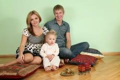 La famiglia si siede sul pavimento sul cuscino Fotografia Stock Libera da Diritti