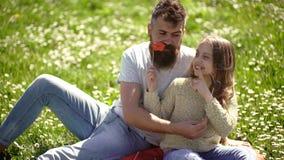 La famiglia spende lo svago all'aperto Il pap? e la figlia si siede su erba a grassplot, fondo verde Posa del padre e del bambino video d archivio