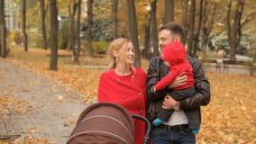 La famiglia splendida passeggia attraverso il parco in autunno in anticipo archivi video