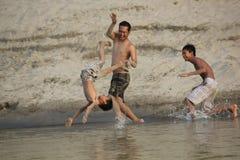 La famiglia sta al gioco il fiume Fotografia Stock