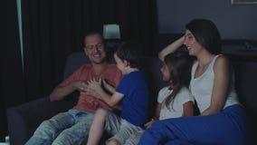 La famiglia sta guardando la TV nella sera archivi video