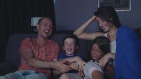 La famiglia sta guardando la TV nella sera stock footage