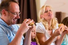 La famiglia sta mangiando l'hamburger o gli alimenti a rapida preparazione Fotografia Stock