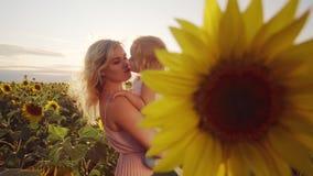 La famiglia sta riposando in natura Una giovane donna con sua figlia nelle sue armi si è nascosta dietro un fiore del girasole Un stock footage