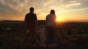 La famiglia sta stando su una collina al tramonto su una sera dell'estate stock footage