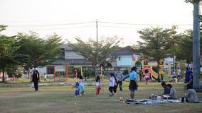La famiglia tailandese asiatica si rilassa il gioco con l'esercizio pareggiante della gente e di picnic al campo da giuoco video d archivio