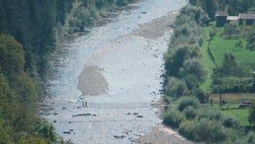 La famiglia va ponte sospeso pedestian attraverso il fiume della montagna in villaggio stock footage