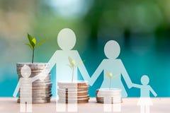 La famiglia vede la pianta crescere nelle monete di risparmio Grafico crescente della pila della moneta dei soldi fotografia stock