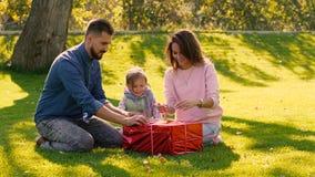 La familia adorable que abre a su pequeña hija es presente de cumpleaños junta almacen de video