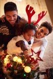La familia adornó el árbol de navidad, padres con la pequeña hija Foto de archivo libre de regalías