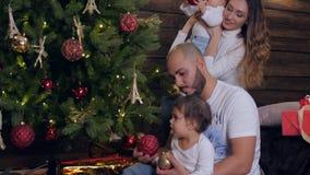 La familia adorna el árbol de navidad, dos niñas con la madre y al padre en víspera de Navidad almacen de metraje de vídeo