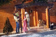 La familia adorna su casa de madera para la Navidad Fotografía de archivo libre de regalías