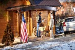 La familia adorna su casa de madera para la Navidad Imagenes de archivo
