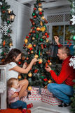 La familia adorna un árbol de navidad Fotos de archivo libres de regalías