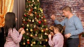 La familia adorna un árbol de navidad con las bolas de oro almacen de metraje de vídeo