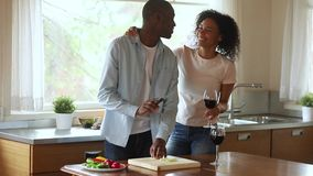 La familia africana feliz joven disfruta de risa del cocinero junta en cocina almacen de video