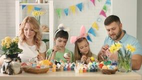 La familia alegre adorna los huevos en la cocina y hace selfies en el teléfono móvil metrajes