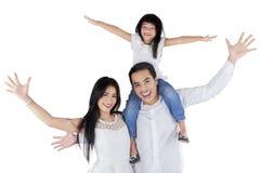 La familia alegre con los brazos para arriba parece feliz Imagen de archivo