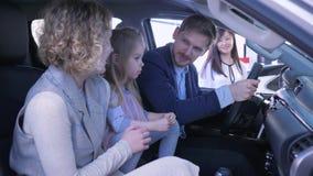 La familia alegre con la pequeña muchacha del niño es feliz de comprar rato del coche para examinar el automóvil en salón en cent almacen de metraje de vídeo